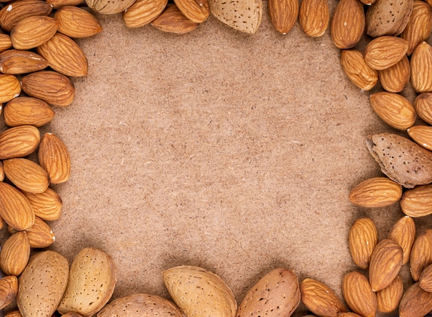 Top view of almond nuts on old paper texture background with copy space