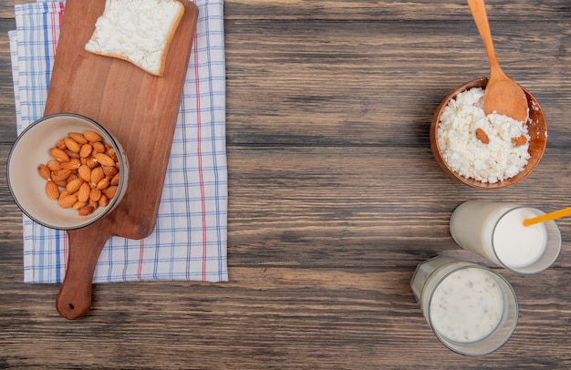 Top view of almonds in bowl and bread slice on cutting board on plaid cloth and cottage cheese milk and yogurt soup on wooden background with copy space
