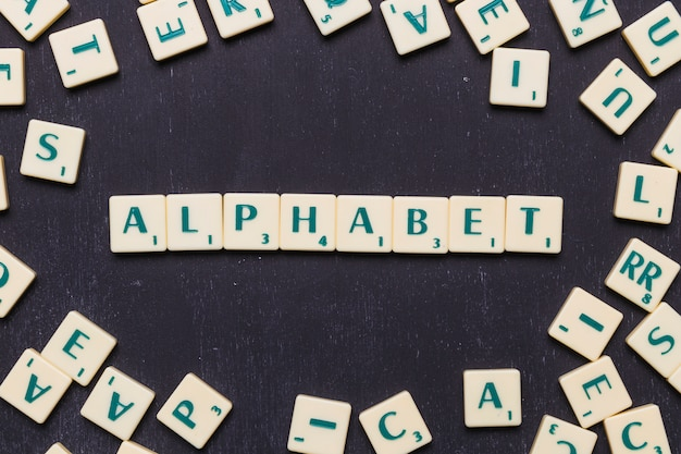 Top view of alphabet text with scrabble letters over black backdrop