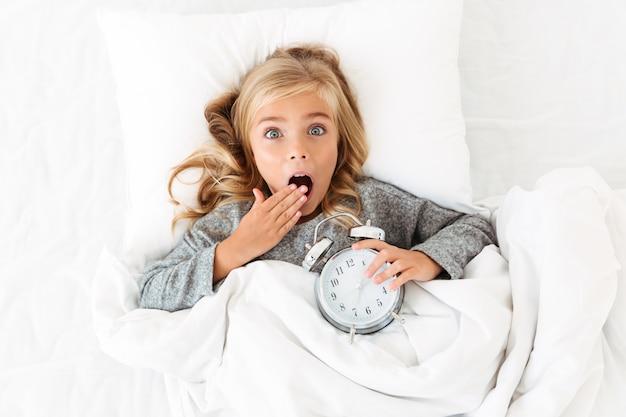 Vista dall'alto della ragazza bionda stupita che copre la bocca con la mano, sdraiata a letto con la sveglia,