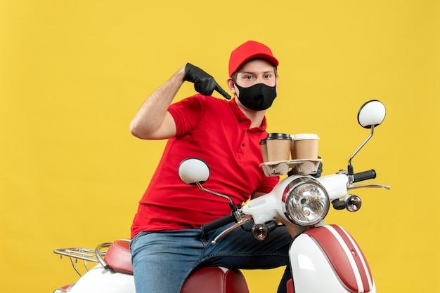 Vista dall'alto del ragazzo delle consegne ambizioso che indossa guanti uniformi e cappello in maschera medica seduto su ordini di puntamento scooter