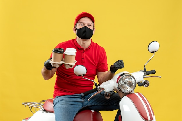 Vista dall'alto del ragazzo delle consegne ambizioso che indossa guanti uniformi e cappello in maschera medica che si siede sullo scooter che mostra gli ordini