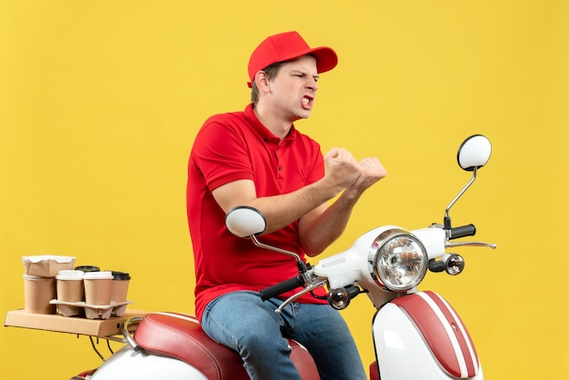 Top view of ambitious emotional young guy wearing red blouse and hat delivering orders on yellow background