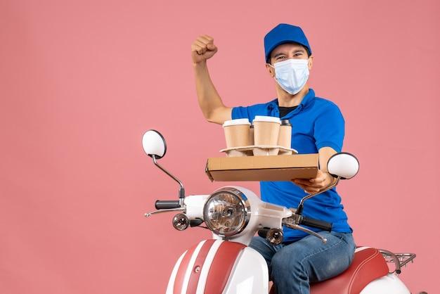 Vista dall'alto dell'ambizioso uomo delle consegne in maschera che indossa un cappello seduto su uno scooter che consegna ordini mostrando il suo muscoloso su sfondo pesca