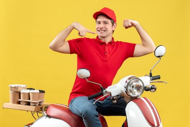 Vista dall'alto del giovane adulto ambizioso che indossa camicetta rossa e cappello offrendo ordine seduto su uno scooter che mostra la sua muscolatura su sfondo giallo