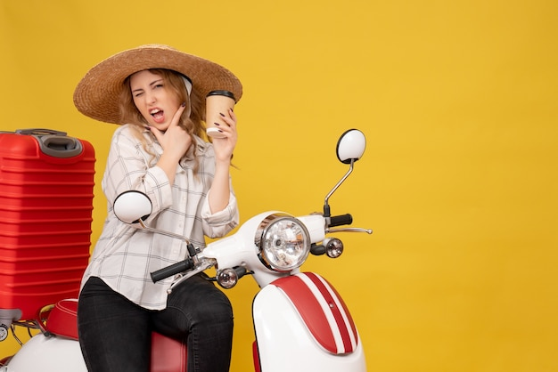 Top view of ambitious young woman wearing hat and sitting on motorcycle and holding coffee