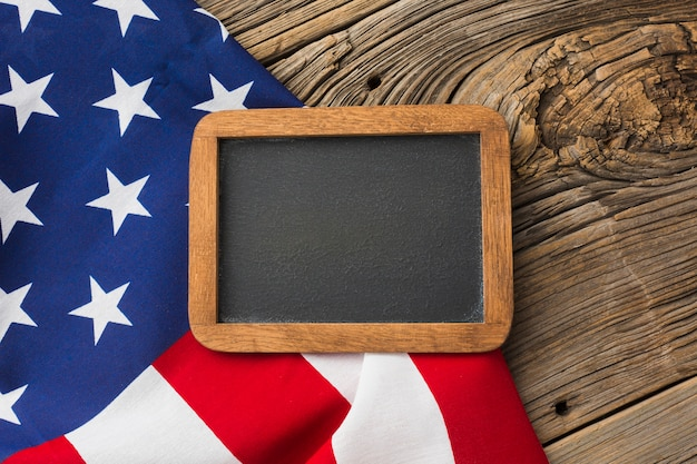 Top view of american flag and blackboard on wood