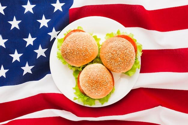 Vista dall'alto della bandiera americana con piatto di hamburger
