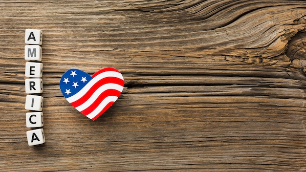 Top view of american heart-shaped flag on wood