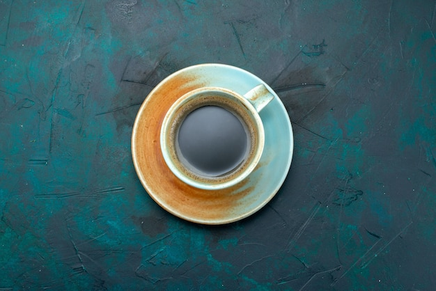 Top view of americano with shadow effect on saucer on dark blue,