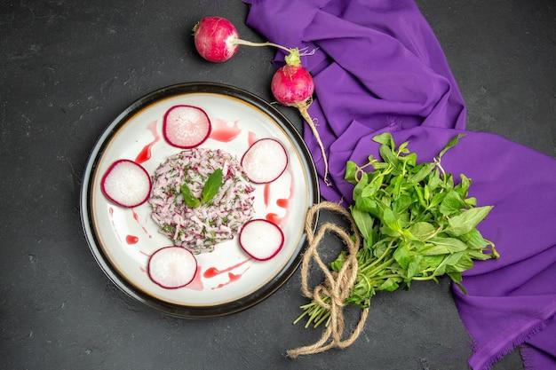 紫色のテーブルクロスの横にあるプレートハーブの食欲をそそる料理大根ソースの上面図
