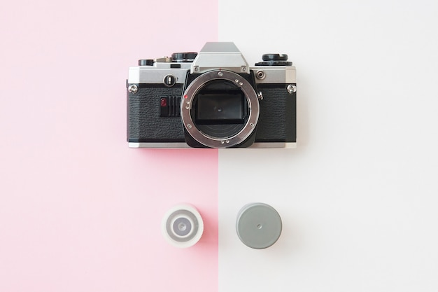 Top view of analaog slr camera with 35 mm film canisters on pink