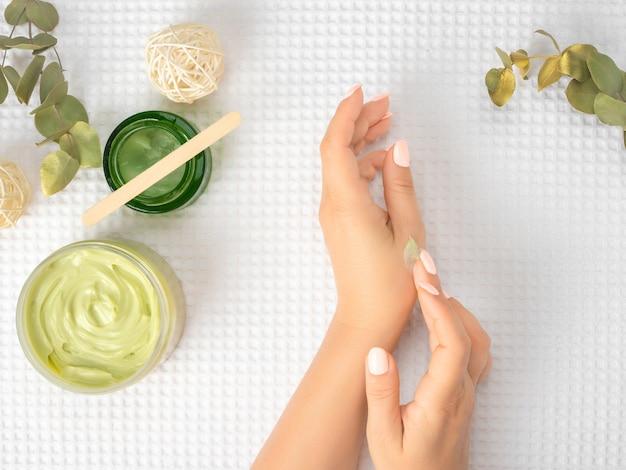 アボカドオイル、クリーム、竹の棒などの化粧品が入った白いタオルの上にクリームを手に持った女性の上面図とフラットレイ。上面図
