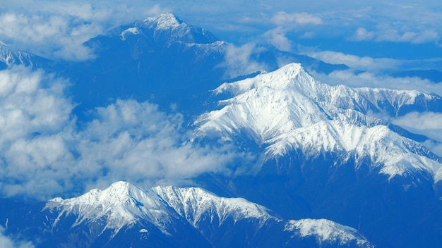 Top view angle images of snow hills around fuji mountain and white light clouds and blue sky in tokyo japan