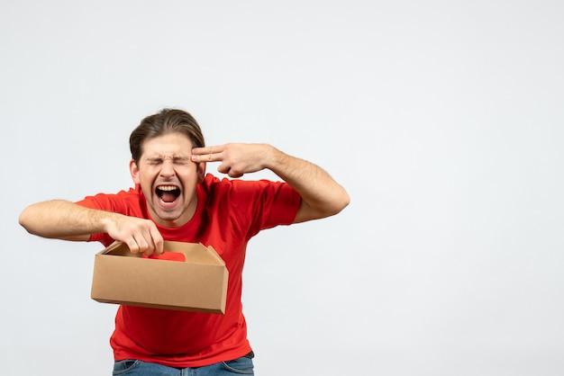 Vista dall'alto del giovane arrabbiato ed emotivo in camicetta rossa che tiene scatola su sfondo bianco