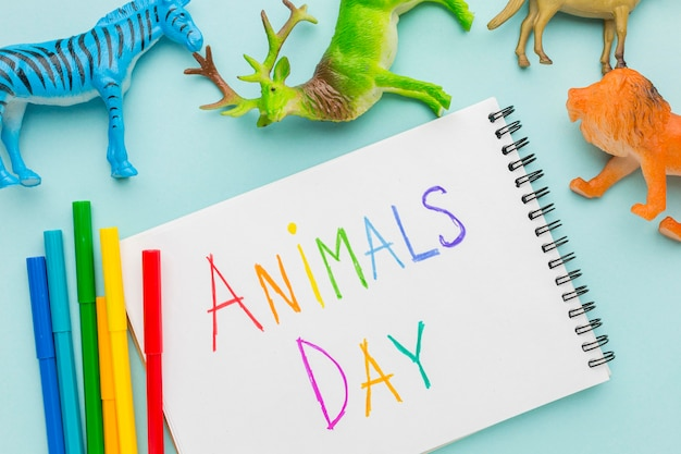 Vista dall'alto di figurine di animali e scritte colorate sul taccuino per la giornata degli animali