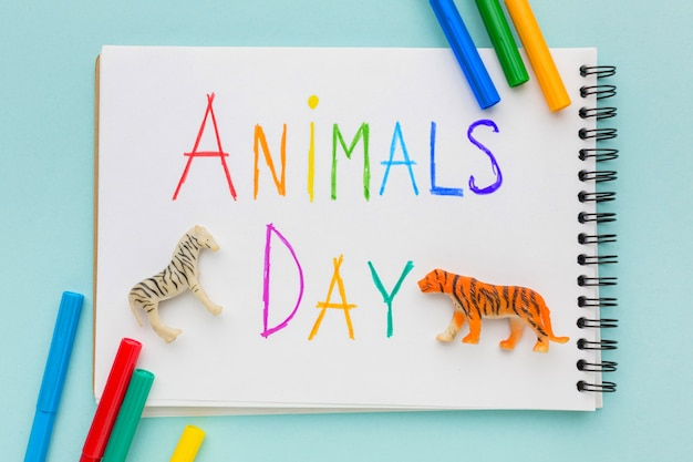 Top view of animal figurines and multicolored writing on notebook for animal day