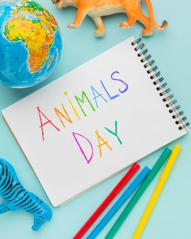 Top view of animal figurines with planet earth and colorful writing on notebook for animal day