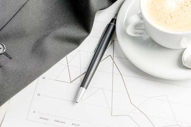 Top view of annual financial business report with coffee and pen on it