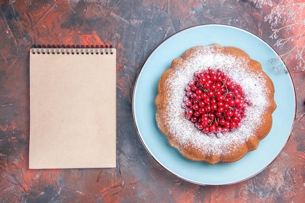 Vista dall'alto una torta appetitosa una torta appetitosa con frutti di bosco accanto al quaderno bianco
