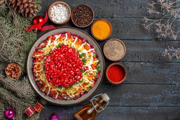 Vista dall'alto piatto appetitoso appetitoso piatto di natale con melograno accanto alla bottiglia di olio spezie rami di albero con coni