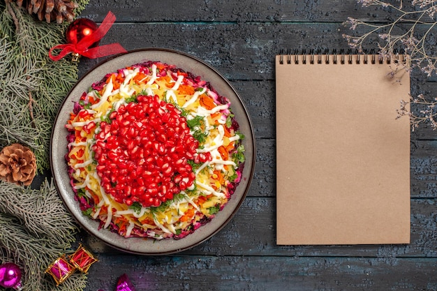 Vista dall'alto piatto appetitoso appetitoso piatto natalizio con melograno accanto ai rami degli alberi e taccuino crema
