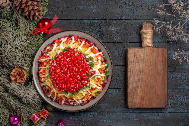 Vista dall'alto appetitoso piatto appetitoso piatto di natale con melograno accanto ai rami degli alberi e tagliere di legno