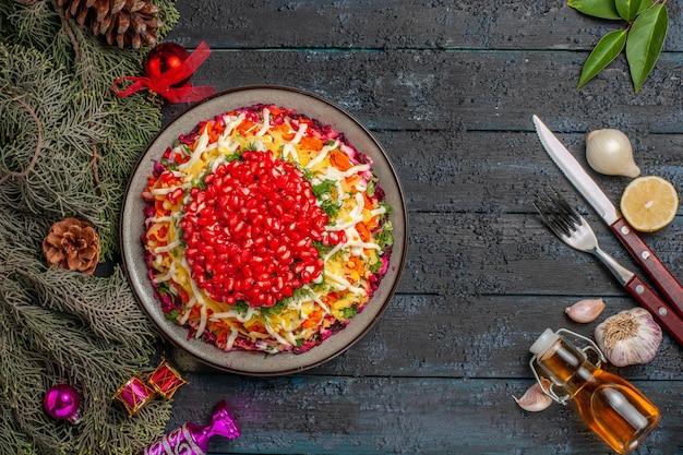 Vista dall'alto piatto appetitoso piatto natalizio con semi di melograno accanto alla bottiglia di olio forchetta coltello rami di albero limone e aglio