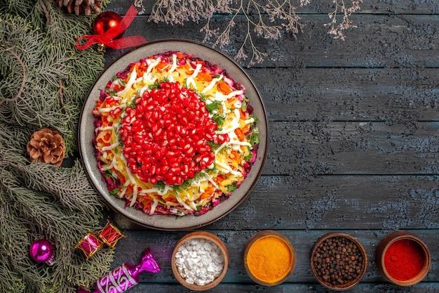 Vista dall'alto piatto appetitoso piatto natalizio con semi di melograno accanto alle ciotole di spezie rami di alberi con coni