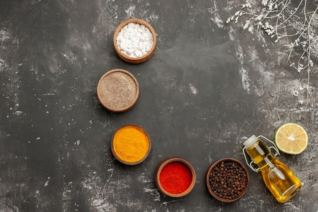 Top view appetizing food bowls of colorful spices bottle of oil and lemon next to the tree branches