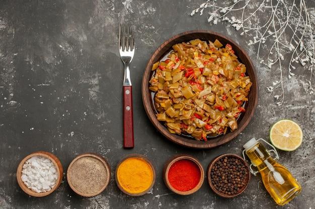 ボウルのスパイスの横にあるサヤインゲンとトマトの食欲をそそる食品の茶色のプレートの上面図フォークレモンと黒いテーブルの上の油のボトル