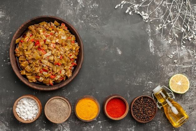 Vista dall'alto appetitoso piatto di fagiolini e pomodori accanto a cinque ciotole di spezie colorate limone e bottiglia di olio sul tavolo