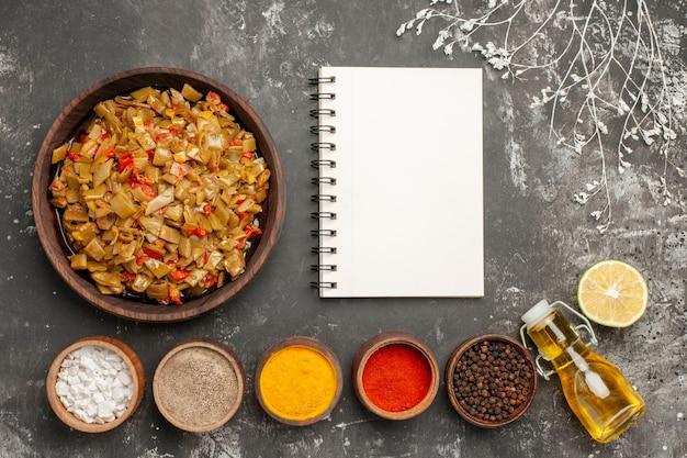 Vista dall'alto cibo appetitoso piatto di fagiolini e pomodori accanto al quaderno bianco cinque ciotole di spezie colorate limone e bottiglia di olio sul tavolo