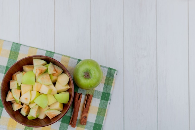 Vista superiore dei cubi di mele in ciotola e intero con cannella sul panno del plaid e fondo di legno con lo spazio della copia