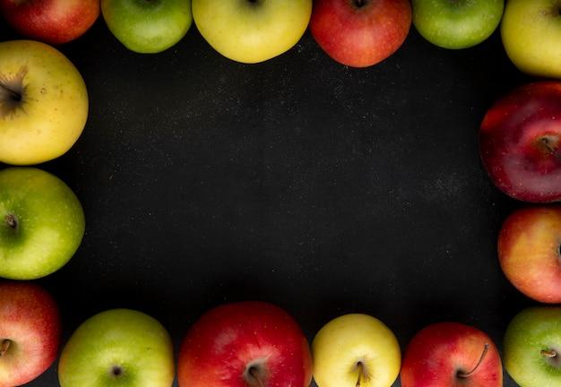 トップビューアップルミックス黒の背景にコピースペースを持つ緑の黄色と赤リンゴ