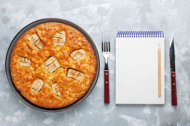 明るい背景にメモ帳付きの鍋の中のトップビューアップルパイシュガーケーキビスケットパイ甘い焼き