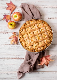 Top view of apple pie for thanksgiving with autumn leaves