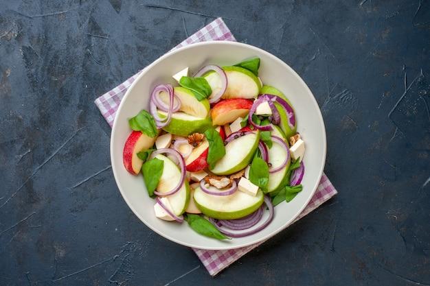 어두운 테이블에 보라색과 흰색 체크 무늬 냅킨 그릇에 상위 뷰 사과 샐러드