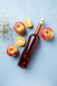 Top view apple vinegar in bottle on white table juice fruit color photo red fresh sour food