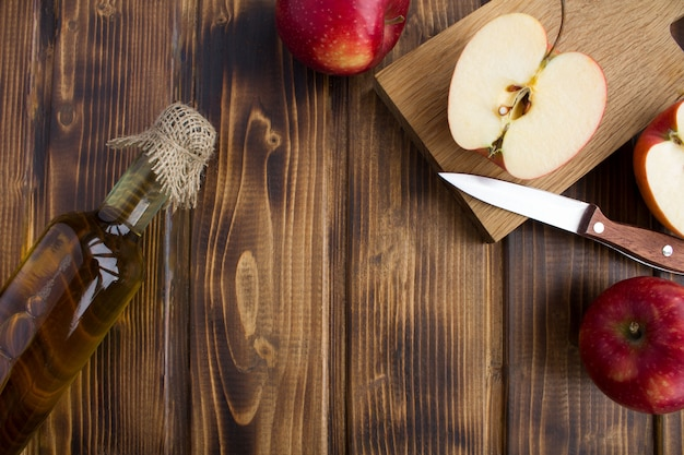 Top view of apple vinegar cider in the glass bottle on wooden surface