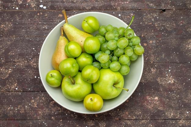 Вид сверху яблоки и виноград вместе с грушами и алычами внутри тарелки на деревянном деревенском фоне фруктовый сладкий мягкий витамин