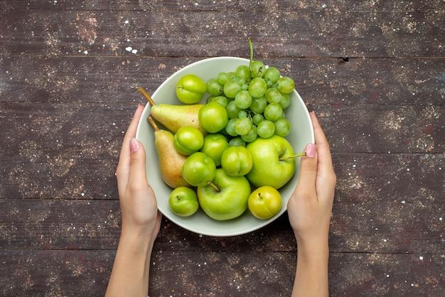 トップビューリンゴとブドウと梨とチェリープラムプレート内の素朴な木製の背景の果物の甘いまろやかな