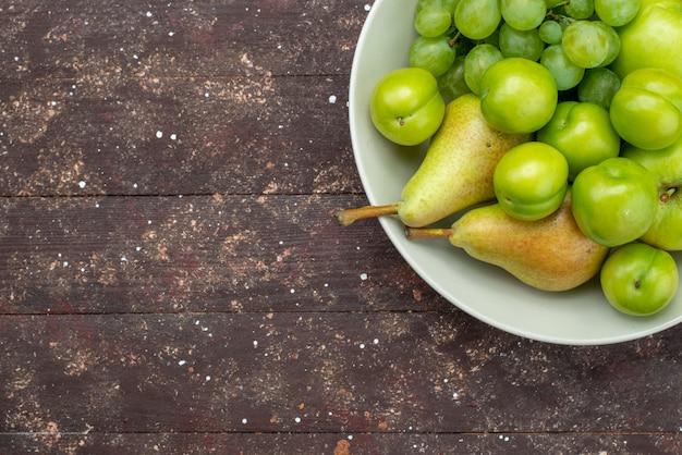 Вид сверху яблоки и виноград вместе с грушами и алычами внутри тарелки на деревянном деревенском фоне фруктовый сладкий спелый