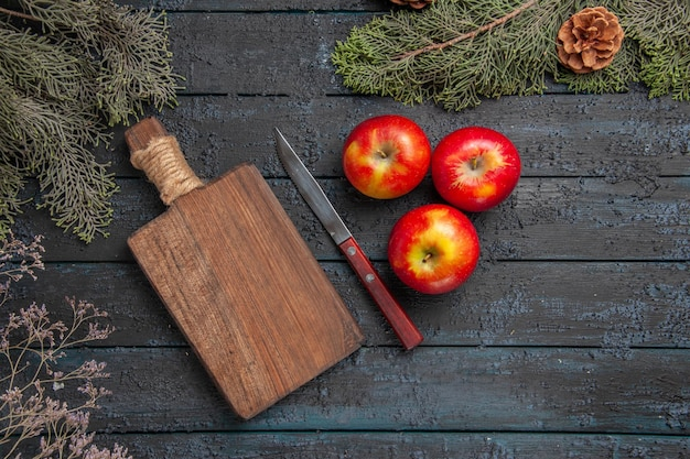 上面図のリンゴとナイフ木製のまな板の横にある3つの黄赤のリンゴと、コーンのある木の枝の下のナイフ