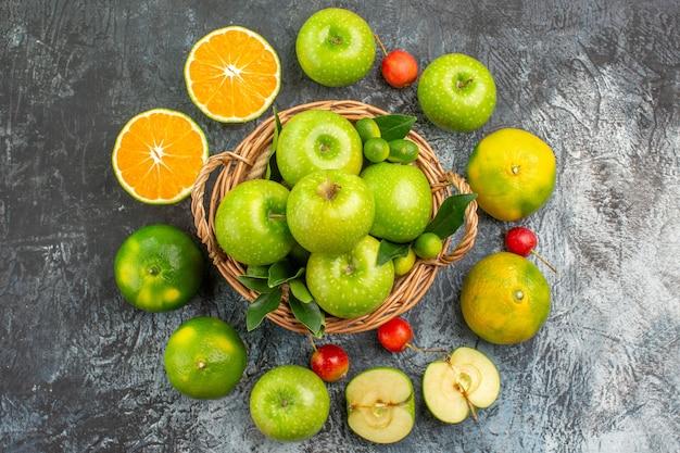 Vista dall'alto cesto di mele di mele verdi agrumi ciliegie