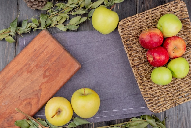 Top view of apples in basket plate and on gray cloth with cutting board and leaves on wooden table