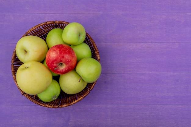 Vista superiore della merce nel carrello delle mele su fondo porpora con lo spazio della copia
