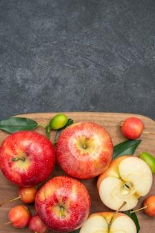 上面図りんごまな板に葉のあるりんごをさくらんぼ