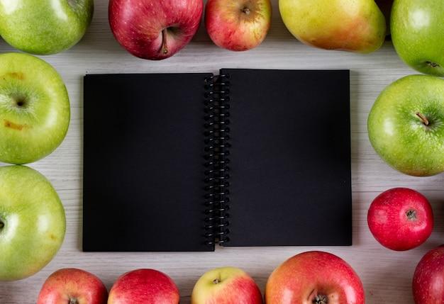Struttura delle mele di vista superiore con il blocco note con lo spazio della copia su di legno bianco