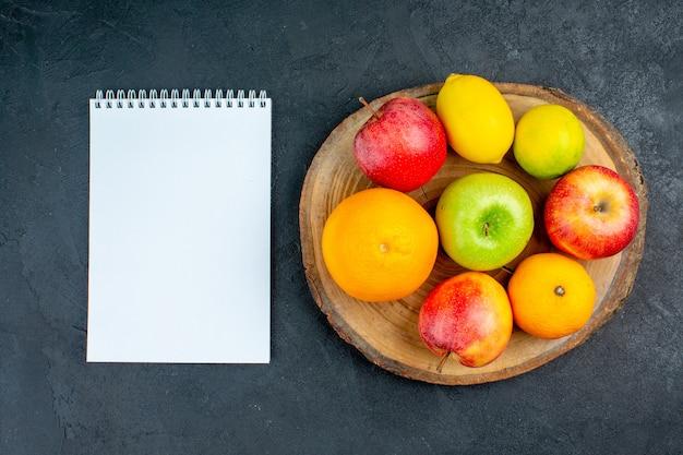 Вид сверху яблоки лимон апельсины на деревянной доске блокнот на темной поверхности